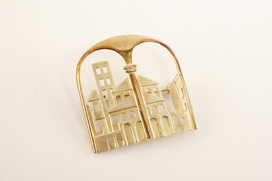 a rare find: a brooch carved to show a southern German city scene, in gold.